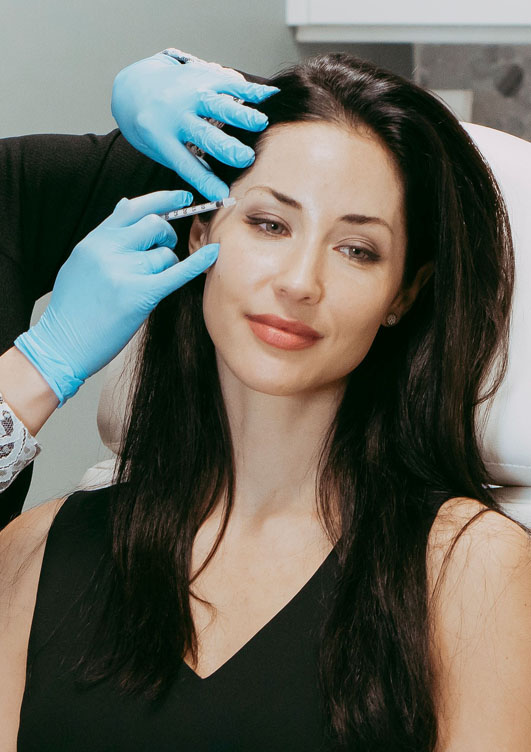 Woman receives injection treatment to remove fine lines around the eyes